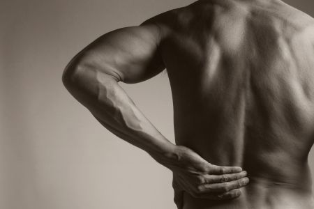 nude back:  a muscular man holding his lower back as if experiencing a backache   Stock Photo