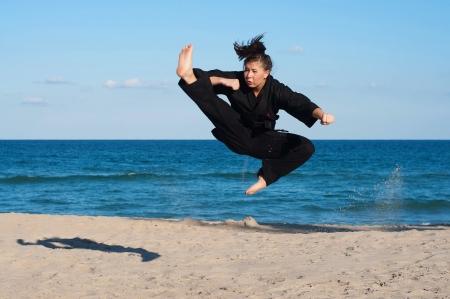 A female, fourth degree, Taekwondo black belt athlete performs a midair jumping kick on the beach   Banco de Imagens