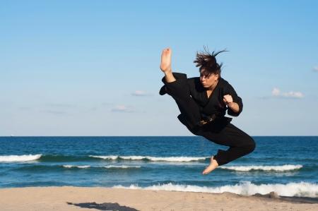 A female, fourth degree, Taekwondo black belt athlete performs a midair jumping kick on the beach Banco de Imagens - 15367123