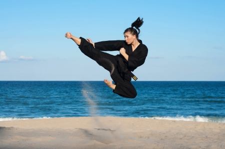 A female, fourth degree, Taekwondo black belt athlete performs a midair jumping kick on the beach   Stock Photo