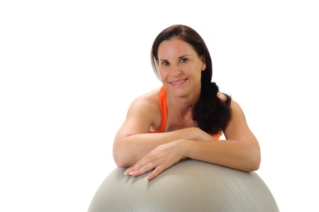 45: Portrait of a beautiful middle aged brunette woman wearing orange workout clothing, smiling and leaning on a gray Pilates exercise ball