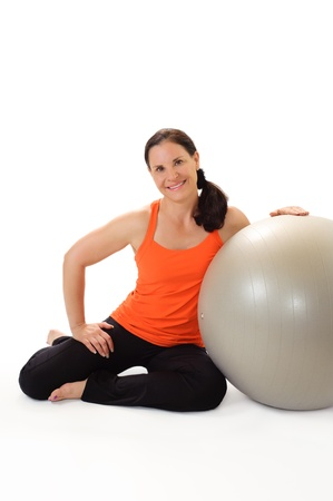 40 45: Portrait of a beautiful middle aged brunette woman wearing orange and black workout clothing, smiling and leaning on a gray Pilates exercise ball   Stock Photo