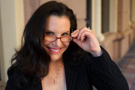 gafas de lectura: Retrato de una atractiva mujer de mediana edad sonriendo y mirando a trav�s de sus gafas de lectura rojo tirado en la localizaci�n con unas oficinas de negocios en el fondo