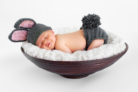 Eight day old smiling newborn baby boy wearing bunny ears and a bunny tail diaper cover  He is sleeping on his stomach in a basket  Shot in the studio on an isolated white background