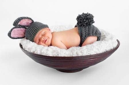 durmiendo: Ocho d�as de edad sonriente beb� reci�n nacido ni�o vistiendo orejas de conejo y una cola de conejo cubierta de pa�al �l est� durmiendo en su est�mago en una canasta de tiro en el estudio sobre un fondo blanco aislado Foto de archivo