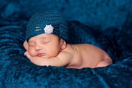 8 day old newborn girl sleeping on a teal blanket and wearing a teal crocheted flapper-style hat with rhinestone embellishment