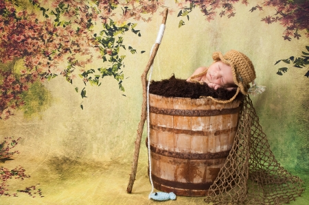 7 day old newborn baby boy sleeping in an old, weathered wooden bucket  He is wearing a crocheted fishing hat and has a stick fishing pole with a crocheted fish on the end of the fishing line   Stock Photo