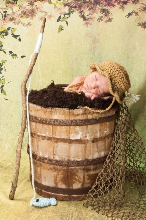 7 day old newborn baby boy sleeping in an old, weathered wooden bucket