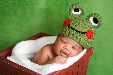 Thirteen day old smiling newborn baby boy wearing a green crocheted frog hat  He is sleeping in a red wooden box  Shot in the studio on a green fuzzy fabric background