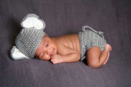 Thirteen day old smiling newborn baby boy wearing a gray crocheted elephant hat and diaper cover  He is sleeping on his stomach on gray fleece fabric
