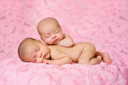 Jumelle des bébés nouveau-nés dorment sur rose, trois dimensions de tissu rose Un bébé est couché sur le ventre et l'autre est calé sur le dessus de sa s?ur