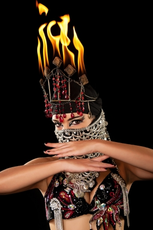 Head and Shoulders shot of an exotic belly dancer wearing a red and black costume with hijab and fire headdress  Shot in the studio on an isolated black background  photo