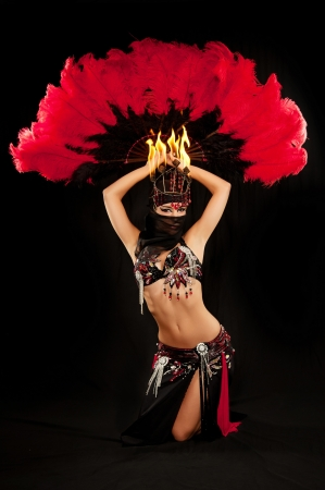 Exotic belly dancer wearing a red and black costume with hijab and fire headdress  She is kneeling and holding a feather fan above her head  Shot in the studio on an isolated black background