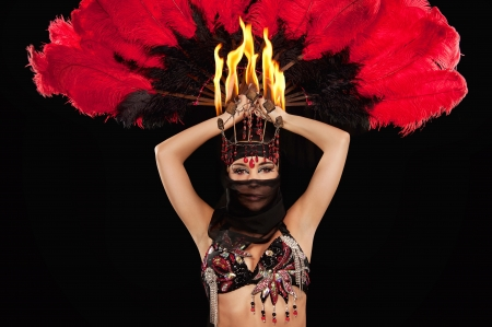 Close up shot of an exotic belly dancer wearing a red and black costume with hijab and fire headdress  She is holding a feather fan above her head  Shot in the studio on an isolated black background   photo
