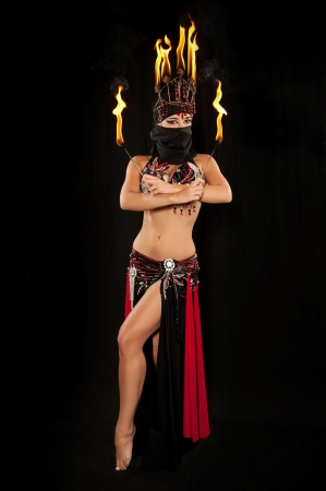 Exotic belly dancer wearing a red and black costume with hijab and fire headdress and holding fire wands  Shot in the studio on an isolated black background  photo