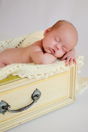Newborn baby girl sleeping in a vintage yellow drawer