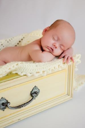 afd088ce353 Pasgeboren baby meisje slapen in een vintage gele lade