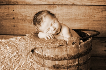 Sepia toned image of an 11 day old newborn baby boy sleeping in an old wooden banded bucket  Shot in the studio with a rustic wood background and hay bail