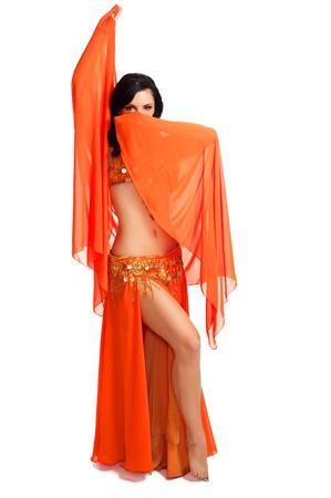 Exotische buikdanseres draagt een oranje kostuum en het houden van een oranje sluier voor haar gezicht Stockfoto