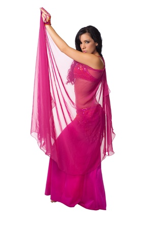 Exotic belly dancer wearing a hot pink costume and wrapped in a hot pink veil  Isolated on white