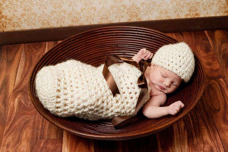 8 day old newborn baby girl sleeping in a crocheted cream colored cocoon  She is wearing a matching beanie hat and lying in a brown bowl  photo