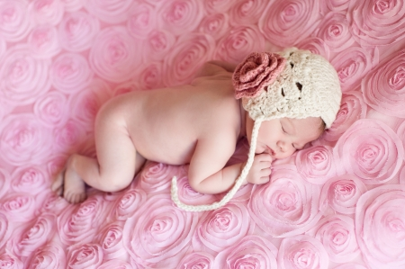 8 day old newborn baby girl wearing a cream colored crocheted bonnet and sleeping on pink rose field fabric