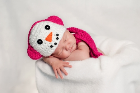 8 day old newborn girl wearing a pink and white crocheted snowgirl costume