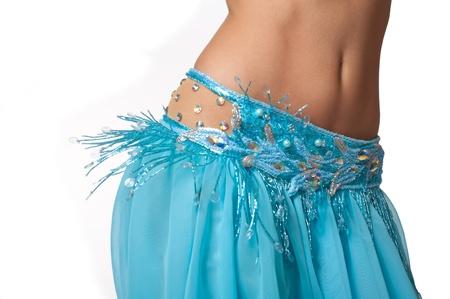 Close-up shot van een buikdanseres draagt een lichtblauw kostuum schudde haar heupen Geïsoleerd op wit