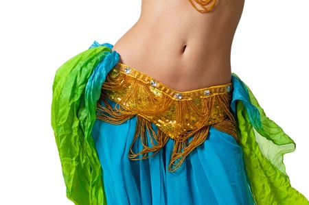 Close up shot of a belly dancer wearing a blue, gold and green costume shaking her hips