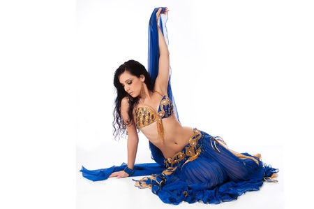 Beautiful belly dancer wearing a blue costume  She is posed on the floor and holding her veil up with one hand  Isolated on white