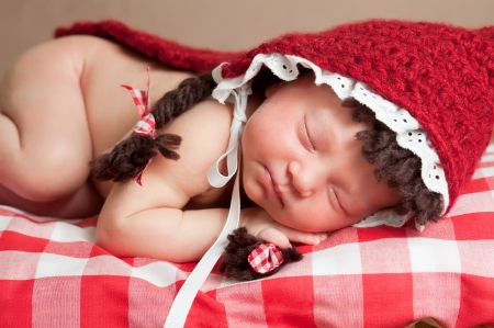 Newborn Baby Girl Wearing a Little Red Riding Hood Costume photo