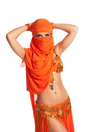 belly dancer: Belly dancer peeking from behind a bright orange veil Stock Photo