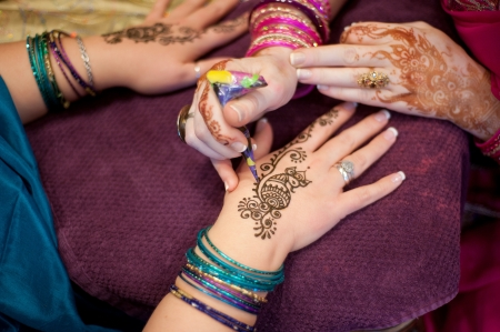 bangles hand: Artist Applying Peacock Henna Design to a Woman�s Hands