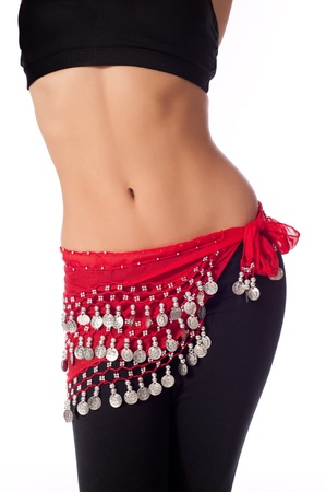 bra top: Torso of an athletic female belly dancer. She is dressed for rehearsing and practicing belly dance wearing a red colored coin belt, black sports bra and leggings. Isolated on white.  Stock Photo