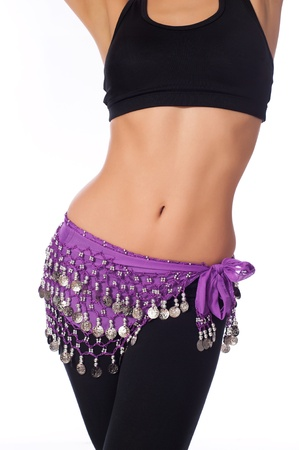 belly dancing: Torso of an athletic female belly dancer. She is dressed for rehearsing and practicing belly dance wearing a lavender colored coin belt, black sports bra and leggings. Isolated on white.  Stock Photo