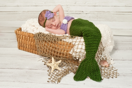 Newborn baby girl wearing a crocheted green and lavender colored mermaid costume, sleeping in a basket with a bleached wood background.