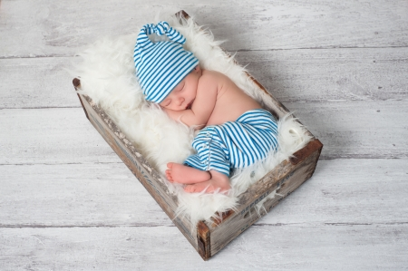 Sleeping Newborn Baby Wearing Pajamas and Sleeping Cap