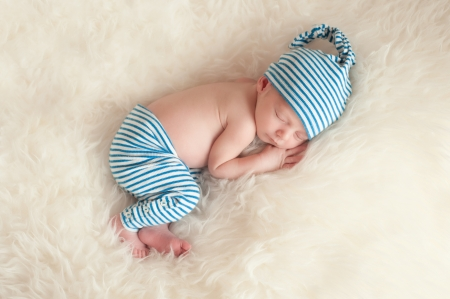 Sleeping Newborn Baby Wearing Pajamas and Sleeping Cap Stock Photo