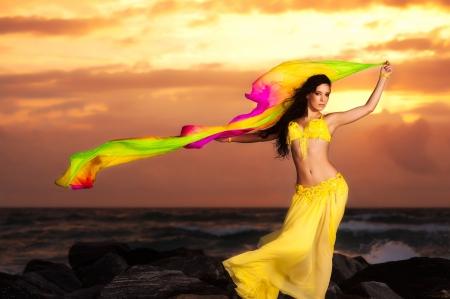 Bauchtänzerin im gelben Kostüm auf dem Strand am Sonnenaufgang