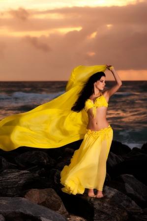 La danseuse du ventre en costume jaune sur la plage au lever du soleil