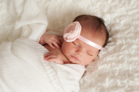babies: newborn baby girl wearing a pink flower headband Stock Photo