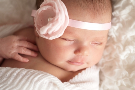 newborn baby girl wearing a pink flower headband Stock Photo