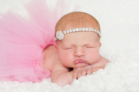 Headshot of a sleeping 8 day old newborn baby girl wearing a pink tutu and rhinestone headband. She is sleeping on her tummy on a white billowy blanket. Imagens