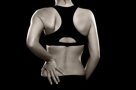 bra: A black and white photo of an athletic woman holding her lower back as if experiencing pain