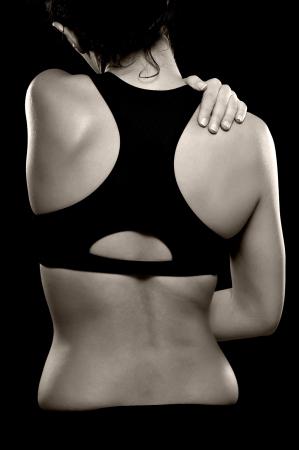 terapia ocupacional: Una foto en blanco y negro de una mujer atl�tica sosteniendo su hombro, como si experimenta dolor Foto de archivo