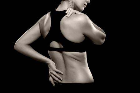 A black and white photo of an athletic woman holding her lower back and shoulder as if experiencing pain Imagens - 20501042