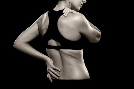 Een zwart-wit foto van een atletische vrouw houdt van haar onderrug en schouder alsof het ervaren van pijn