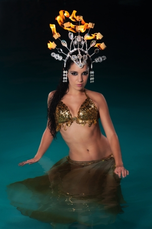 Portrait of an exotic, wet belly dancer standing waist deep in blue water wearing a a gold costume with a fire headdress  photo