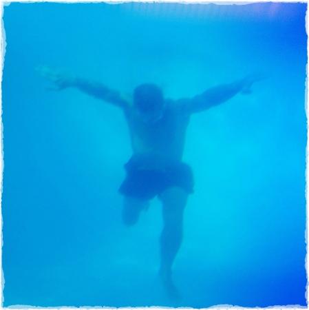 ahogarse: Underwater foto de un hombre en buena forma física que salta en una piscina.