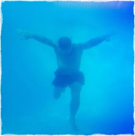 physically: Underwater shot of a physically fit man jumping in a swimming pool.